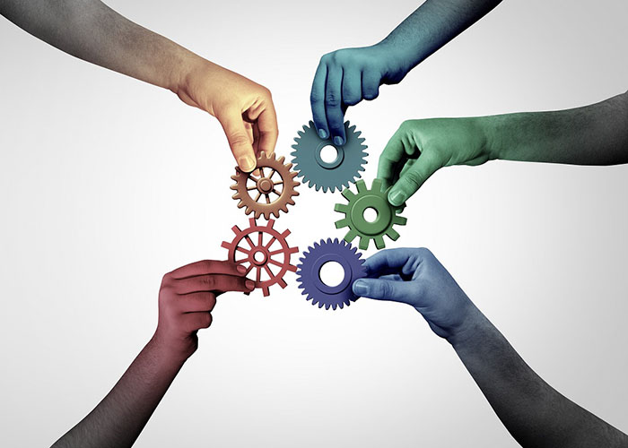 colorful arms and hands reaching in with gears