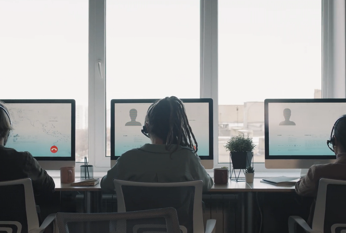 call center agents in front of computers lined up in front of large window