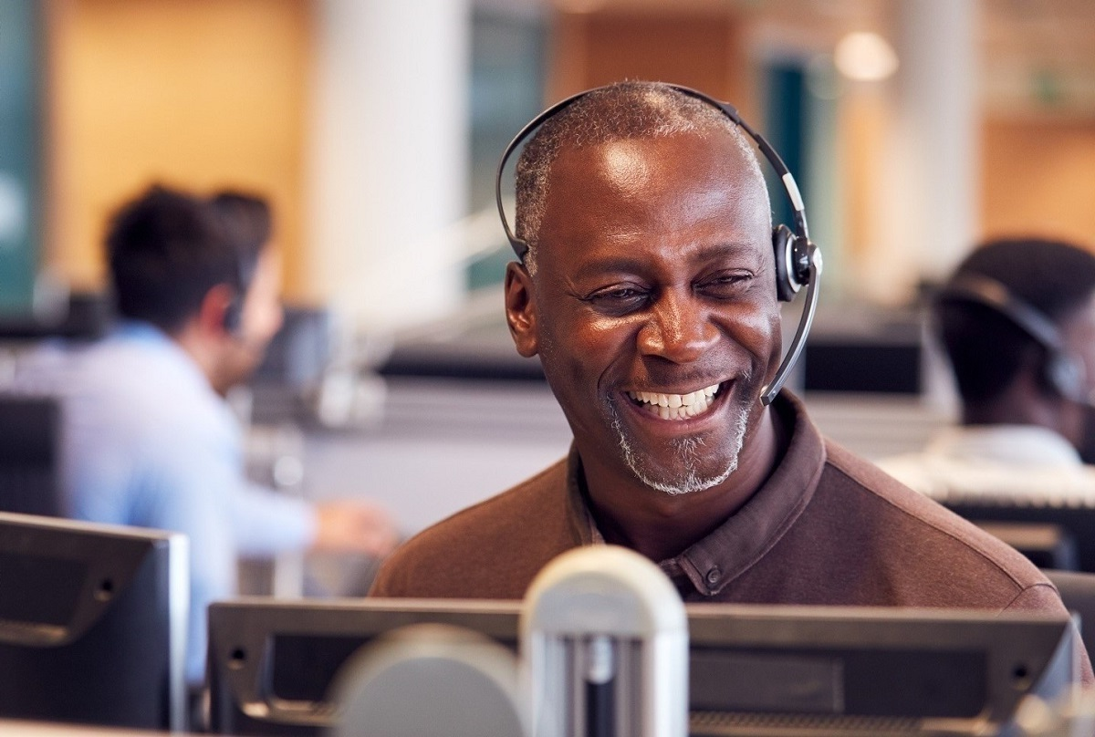 older man in headset smiling in front of computer