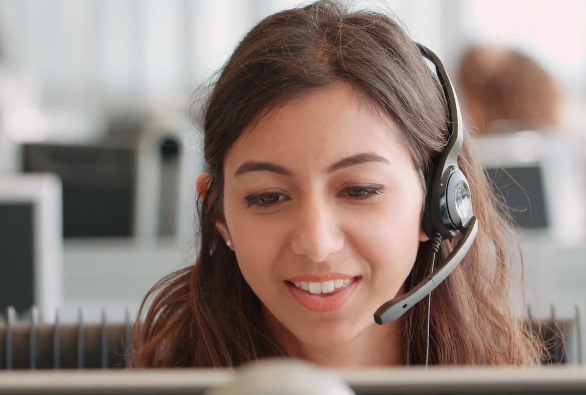 brown haired woman with headset talking with customer