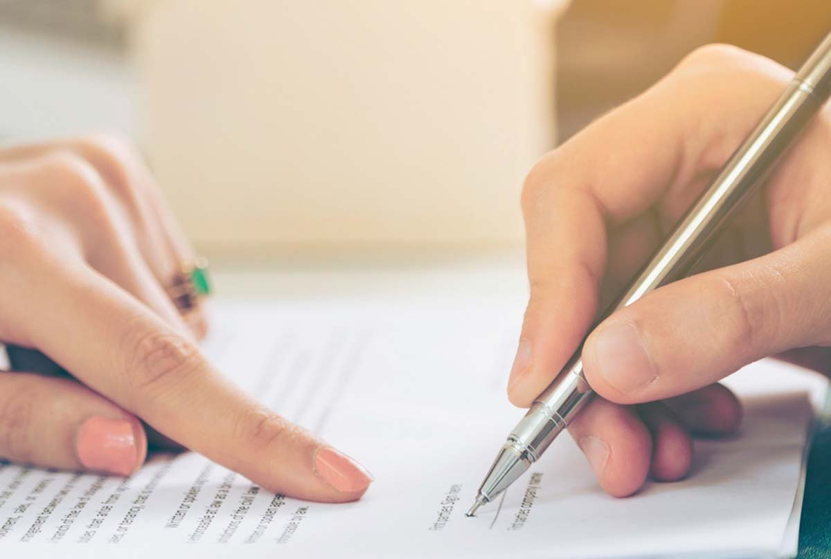 woman pointing to line on contract while man signs