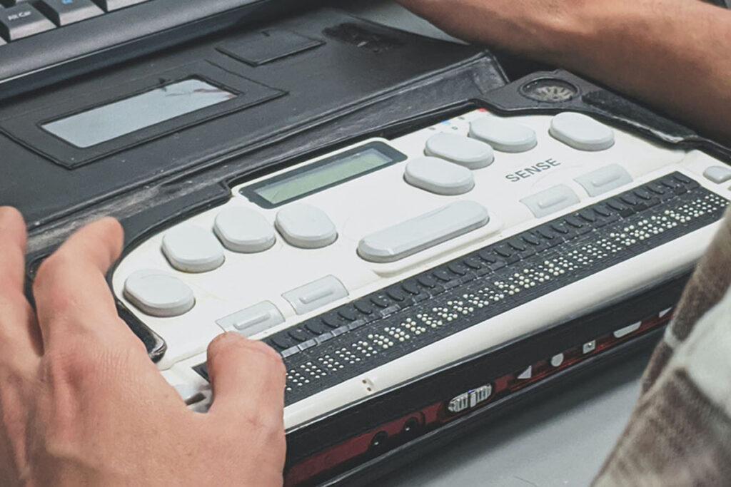 man using braille typewriter
