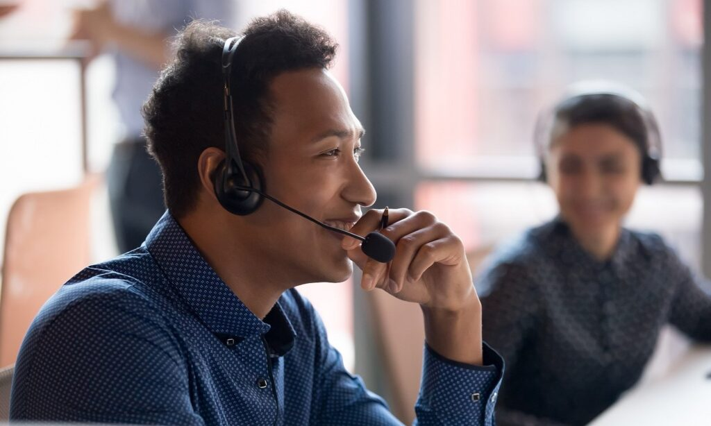 man on headset smiling while another agent looks on