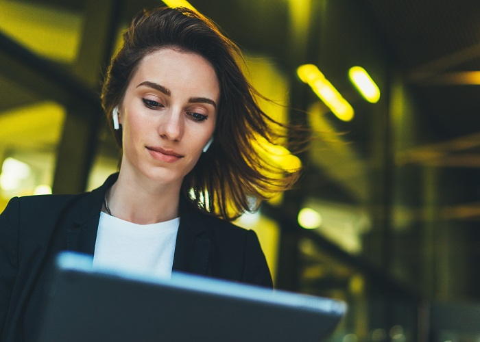 business woman on laptop with breeze blowing through hair
